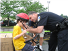 Officer Helps Young Child Latch Helmet