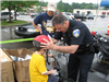 Officer Stands With Small Child While Putting on Helmet