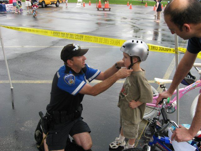 Officer Assist Child With Helmet Latching