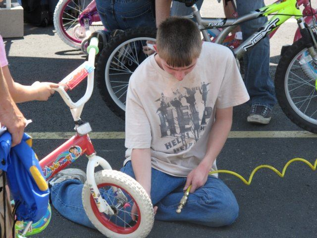 Young Volunteer Airs Up a Tire