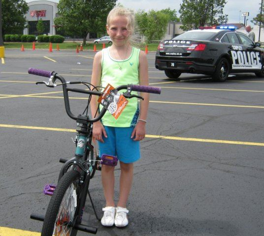 Young Girl Stands Next to Bike