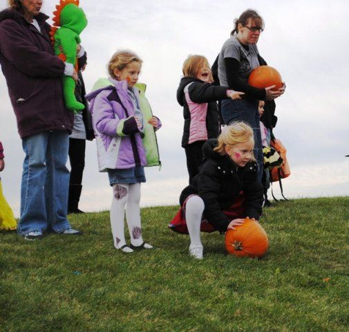 Young Girls Roll Pumpkin Down Hill