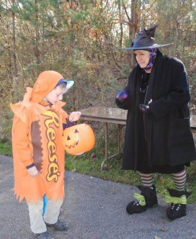 Woman in Witch Costume Giving Out Candy