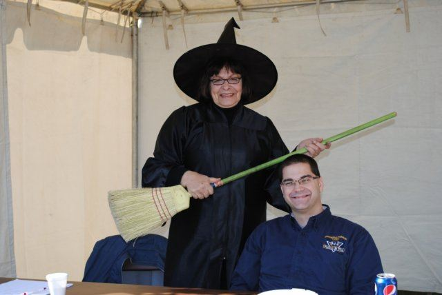 Woman in Witch Costume Smiles With Volunteer