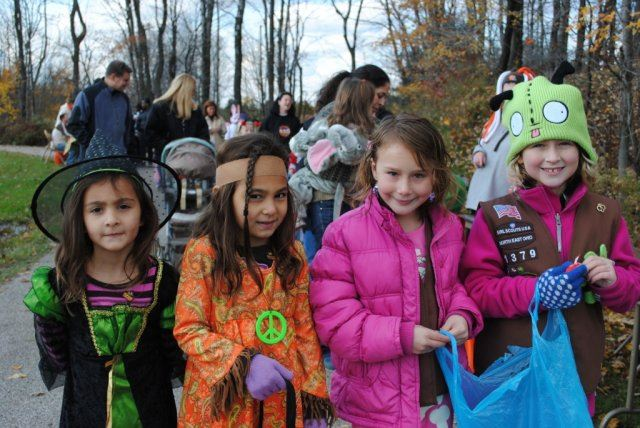Young Children Wear Costumes as They Go Towards Candy