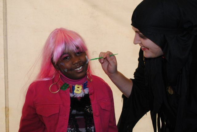 Young Girl Smiles While Getting Face Painted